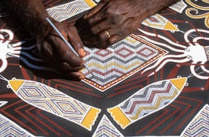 The Aboriginal artist Terry Yumbulul paints sea creatures in Arnhem Land