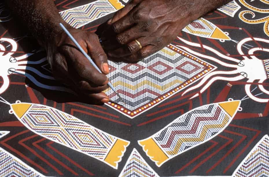 The Aboriginal artist Terry Yumbulul paints sea creatures in Arnhem Land