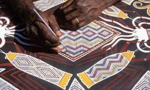 An Aboriginal artist painting sea creatures
