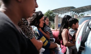 Dozens of women, men and their children, many fleeing poverty and violence in Honduras, Guatamala and El Salvador, arrive at a bus station following release from Customs and Border Protection on Saturday in McAllen, Texas.