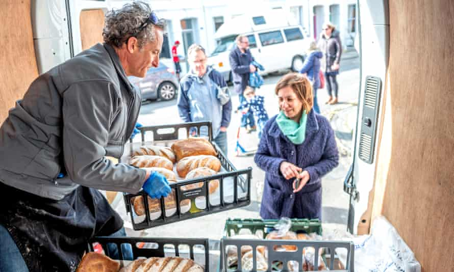 A baker who is no longer able to supply restaurants sells bread to Brighton residents yesterday from the back of his van.