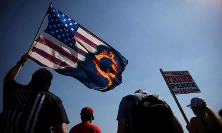 A supporter of President Donald Trump holds an U.S. flag with a reference to QAnon