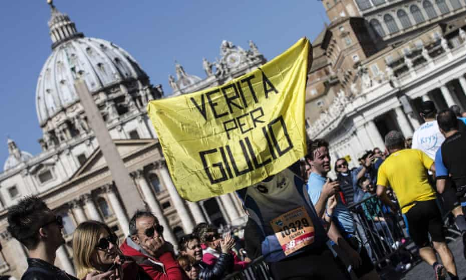 A demonstrator holds a banner demanding 'Truth for Giulio' in front of St Peter's Basilica.