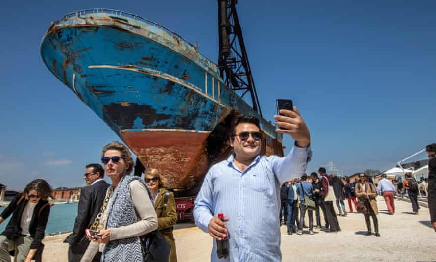 A man takes a selfie in front of Barca Nostra, at Venice Biennale
