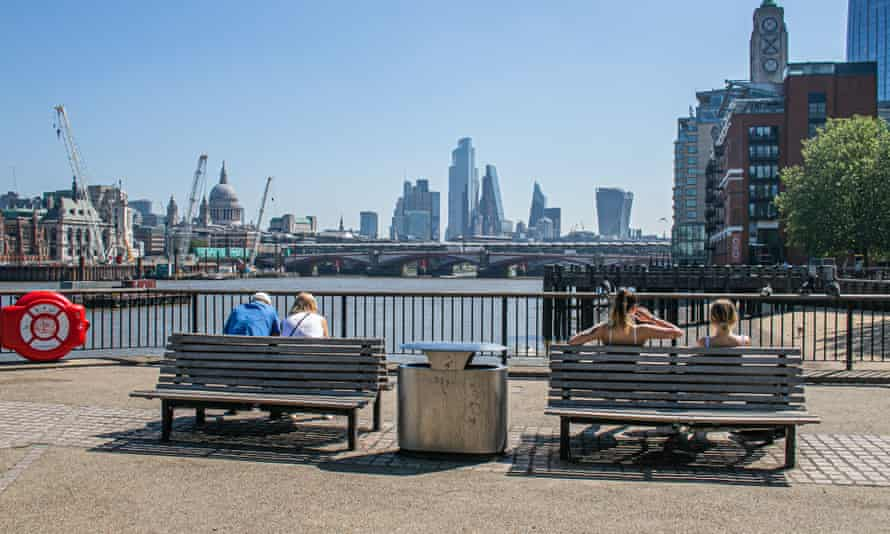 People on benches in the sunshine on London's South Bank looking across to the city skyline and financial district
