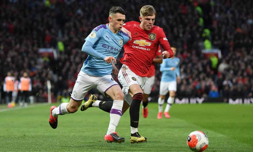 Phil Foden takes on Brandon Williams in the Manchester derby.