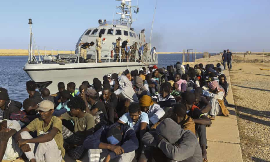 Rescued refugees and migrants sit next to a coastguard boat in Khoms, Libya, October 2019