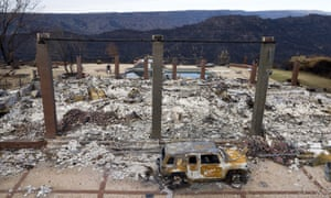 A vehicle rests in front of a home leveled by the Camp fire in Paradise, California.