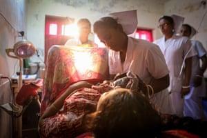 Midwife, Bimola Kobiraz, 29, delivers newborn baby to mother, Hera, 20, at Dacope Upazila Health Complex, Chalna, Dacope, Khulna, Bangladesh