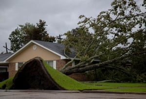 An uprooted tree tears up the lawn outside a house as Hurricane Ida hits Morgan City.