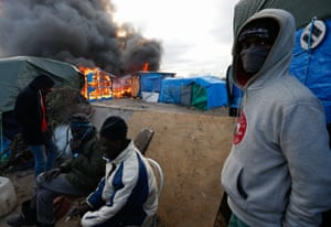 Refugees in front of a burning shelter.