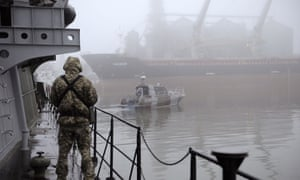 A Ukrainian soldier stands guard aboard a military ship moored in Mariupol port on the Sea of Azov