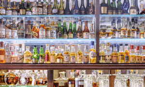 Wall of cognac bottles at the bar of Restaurant Le Chai in Cognac, France.