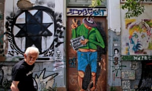 epa04790772 An elderly man walks in front of a house covered in graffiti in central Athens, Greece, on 09 June 2015. Greece has submitted new reform proposals to its creditors, sources in Brussels say, a day before Greek Prime Minister Alexis Tsipras is due to hold key talks with German Chancellor Angela Merkel and French President Francois Hollande. Meanwhile, government sources in Athens say talks late Monday between the country's lead negotiator, Euclides Tsakalotos, and EU Economy Commissioner Pierre Moscovici led to no breakthrough. EPA/SIMELA PANTZARTZI