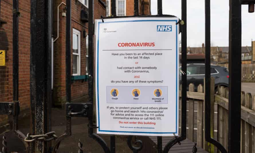 An NHS coronavirus sign attached to the gate of a primary school in London.
