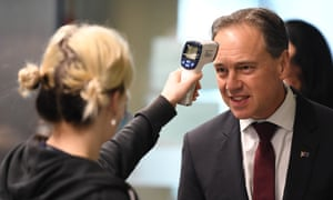 Federal health minister Greg Hunt has his temperature checked before touring the Royal Melbourne Hospital in June.
