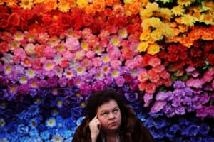 Minsk, Belarus A woman sits in front of a wall of artificial flowers during the International Memorial and Stone Working fair