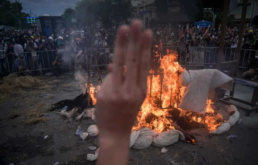 A protester makes a three-finger salute as they burn effigies signifying coronavirus victims.