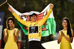 Geraint Thomas holds the Welsh flag as he celebrates on the podium.