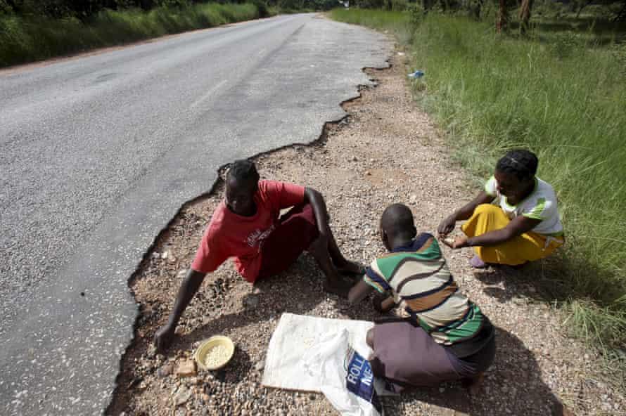 Women gather grain spilled by cargo trucks from Zambia along a highway in Magunje, Zimbabwe