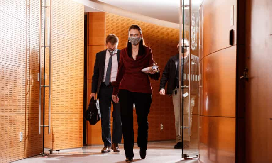 New Zealand prime minister Jacinda Ardern walks through a doorway, followed by the director general of health, Ashley Bloomfield, both wearing masks