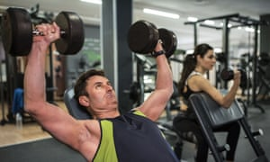 A man and a woman work out in a gym