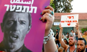 Members of Israel's LGBT population hold a banner reading in Hebrew 'A homophobic racist has to quit' during a rally against Rafi Peretz in Tel Aviv.