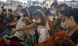 Customers wearing face masks buy clothes for one euro at a stall in a market in Barcelona on Wednesday.