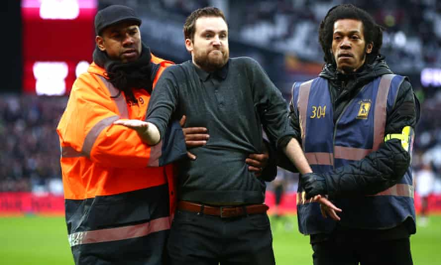A pitch invader is led away during the match between West Ham and Burnley.