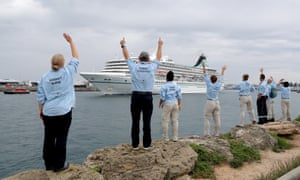 Australian Medical Assistance Team (Ausmat) staff who worked with the passengers and crew of the Artania wave goodbye as it departs Fremantle harbour