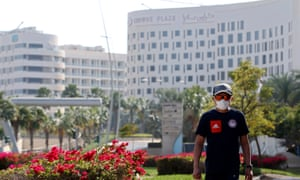 A man wearing a face mask walks in front of the Crowne Plaza hotel where Cofidis team members have been confined to the fourth floor.