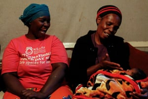 Jackline Bosibori's mother Ann Kemunto sits with a friend as they spend time with Bosibori's newborn daughter in Lindi village