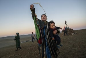 A shaman holds her child while throwing milk