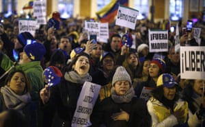 People gather during a protest Venezuela's Nicolas Maduro and in support of an opposition leader self-proclaimed as the interim president of the country in Madrid, Spain, Wednesday, Jan. 23, 2019. Around 7,000 protesters according to organizers, gathered in a central square of the Spanish capital, where a significant Venezuelan community has grown in recent years with people fleeing persecution or poverty at home