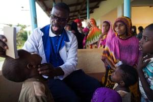 Nurse Kalu Harrison examining a young boy from Mtangawanda village in Lamu, Kenya