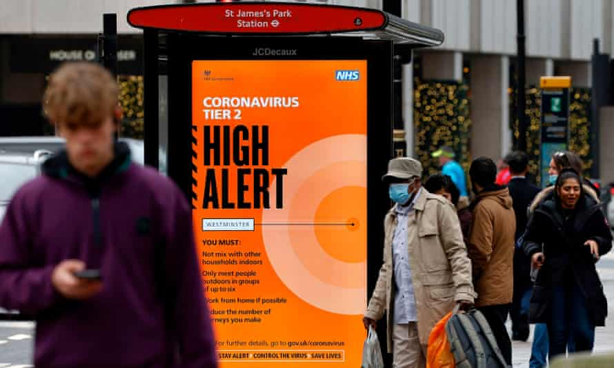 Pedestrians walk past Tier 2 Coronavirus information displayed on an electronic advertising board at a bus stop in central London