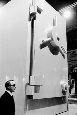 A man in a black suit and dark glasses stands near an imitation of a giant bank safe in the main hall of Zurich railway station