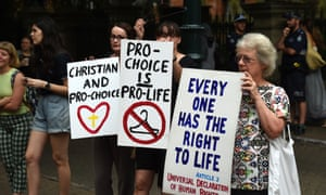 Pro-choice supporters (left and centre) stand next to a an anti-abortion protester during a rally outside the Queensland Parliament in Brisbane.