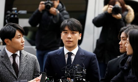 Big Bang member Seungri, centre, who admitted to secretly filming himself with at least ten women.