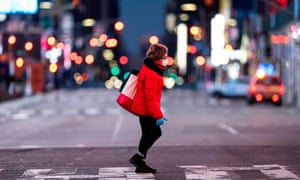 A woman walks through an almost-deserted Times Square in the early morning hours in April.