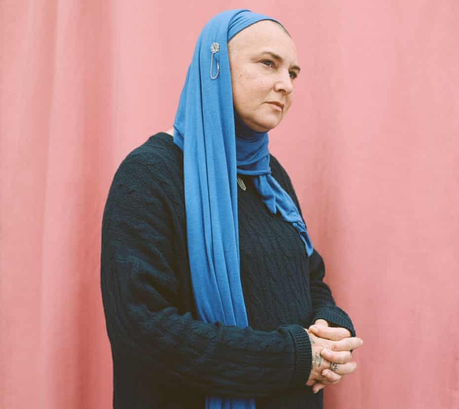 Sinead O'Connor wearing black jumper and blue headscarf against pink background
