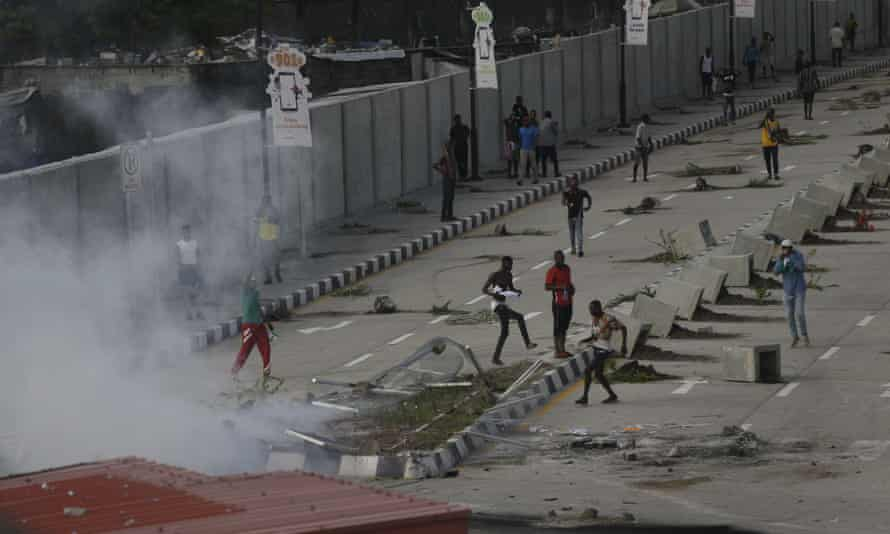 Protesters stand in the street in Lagos as police officers fire teargas