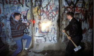 People smash chunks off the Berlin Wall on 12 November 1989