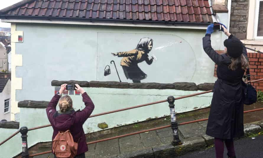 People take pictures of the new Banksy artwork
