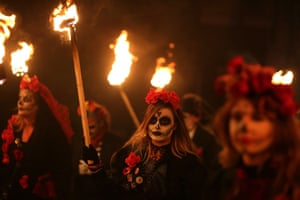 Face-painted revellers parade through the streets of Lewes in East Sussex