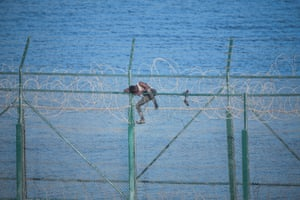 A migrant attempts to jump the barbed-wire border fence that separates Morocco from Spain's north African enclave of Ceuta.