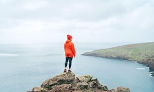 Trail runner dressed orange sporty hoodie and red cap resting on the cliff and enjoying Atlantic ocean view on Ponta de Sao Lourenco peninsula