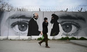 A man walks past a mural of the US special representative Zalmay Khalilzad, left, and the Taliban co-founder Mullah Abdul Ghani Baradar in Kabul