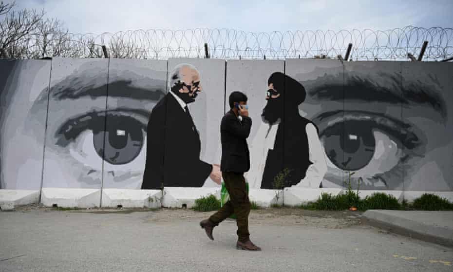 A man walks past a mural of the US special representative Zalmay Khalilzad, left, and the Taliban co-founder Mullah Abdul Ghani Baradar in Kabul