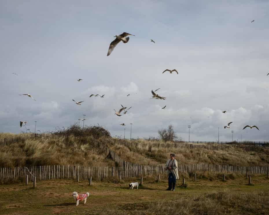 A woman walks her dogs near the coast at Ouistreham.